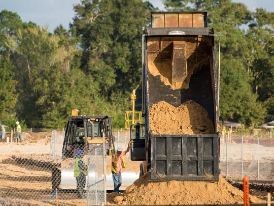 Workers move dirt at the location of a Department of Veterans Affairs outpatient clinic in Lafayette, La., Wednesday, Nov. 11, 2015.