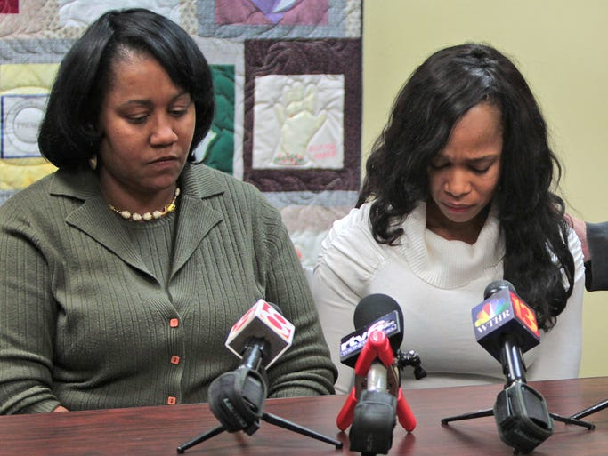 Shirley Justice's friend Tanisha Cohen, center, becomes emotional as she talks about her friend, lying in a hospital after being shot 13 times by her ex-husband.  Justice's mother, Sheila Hart, left, and attorney Virgene Cline, right, listen, during a press conference at the Indiana Coalition Against Domestic Violence offices, Thursday, February 27, 2014.  They were responding to today's court hearing reducing the bond of Christopher Justice accused of shooting his ex-wife Shirley Justice last week outside a day care center.