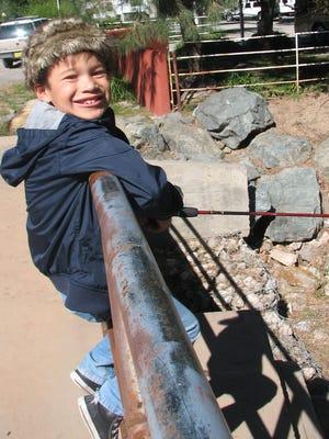 Johnny Alvarado, 7, from El Paso tries his fishing technique off a bridge over the Rio Ruidoso.
