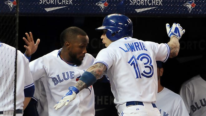 Toronto Blue Jays second baseman Brett Lawrie is greeted at the dugout steps by shortstop Jose Reyes after hitting a fifth-inning home run against St. Louis Cardinals at Rogers Centre.