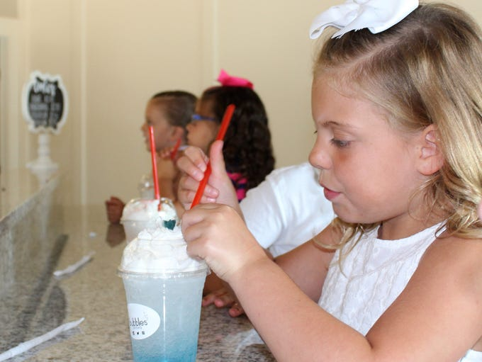 A young customer sips a specialty soda at Bubbles Drinks,
