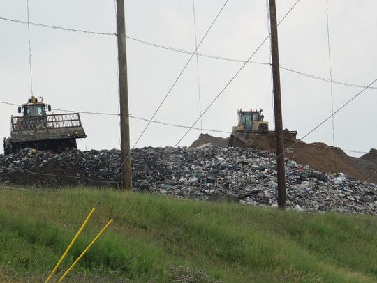 Bulldozers move freshly dumped trash at Ontario County