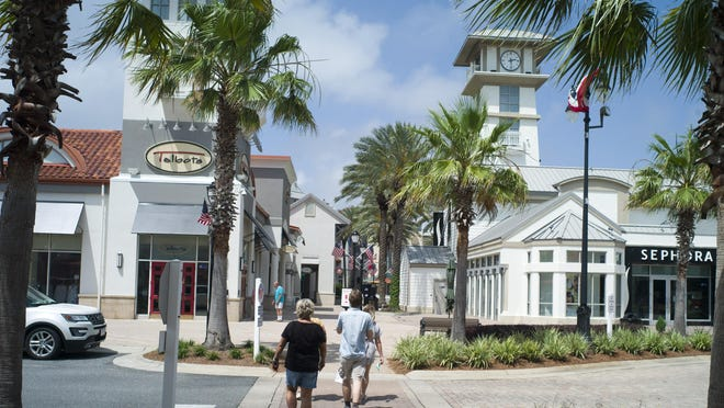 Shoppers walk near the roundabout in Destin Commons.