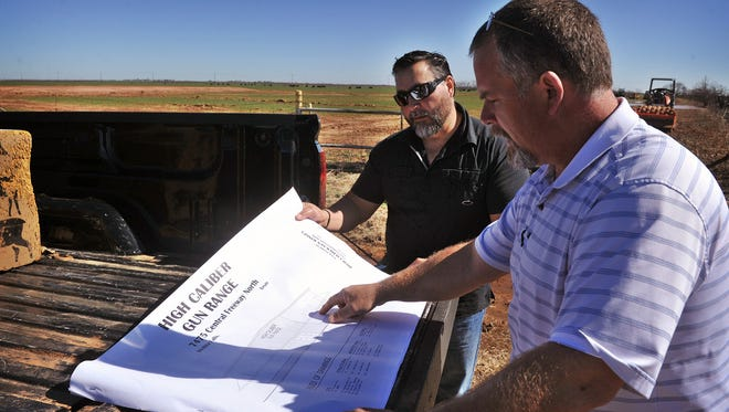 Mickey Fincannon, right, and Bobby Hulett look over the building plans for their business venture, High Caliber Gun Range, in the 7000 block of Central Freeway North, near Bacon Switch Road. The 13,000-square-foot facility will feature a 10-lane indoor range, classrooms, retail, and gun rental.