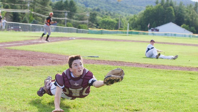 Asa Hoover playing catcher for Franklin County dives for a foul ball at an American Legion baseball game against Addison County.