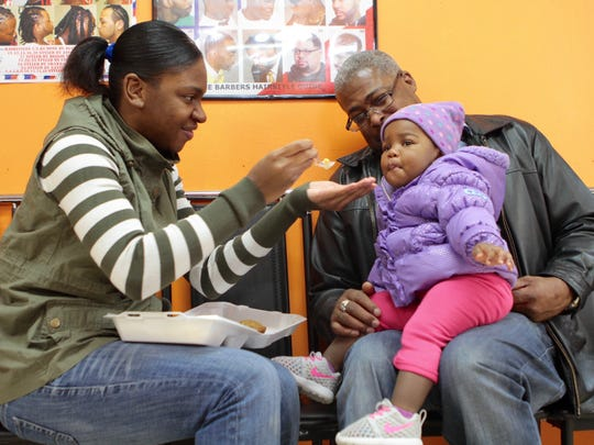 Tierenny Davis, of Rochester, left, feeds daughter N'yliah, 1, part of a Thanksgiving meal at Brothers & Sisters Unisex Salon Thursday.