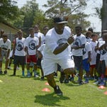 Trent Richardson demonstrates football moves to young players Saturday during the Trent Richardson Football Camp at Escambia High School. Richardson signed with the Baltimore Ravens on Monday.