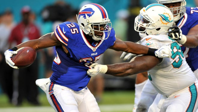 Buffalo Bills running back LeSean McCoy (25) is tackled by Miami Dolphins defensive tackle Earl Mitchell during the first half at Sun Life Stadium.