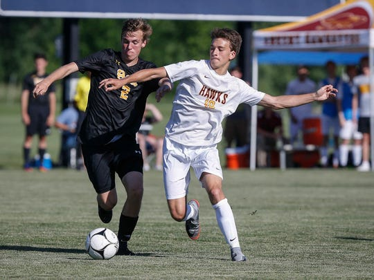 Ankeny junior Kolby Raineri, right, moves the ball