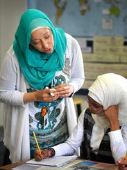 Alana Raybon helps Iman Omer with a lesson Wednesday