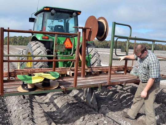 Bryan Jones inspects a tractor he uses to bury underground drip irrigation on his family's farm in Elkton, Fla.