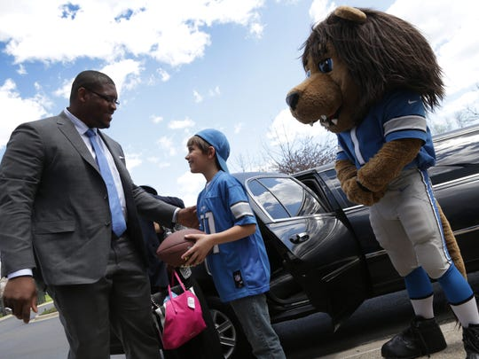 Laken Tomlinson is greeted by Lions fan Michael Kapuscinski, 11, of Saginaw Twp. at Lions headquarters in Allen Park on May 1, 2015.