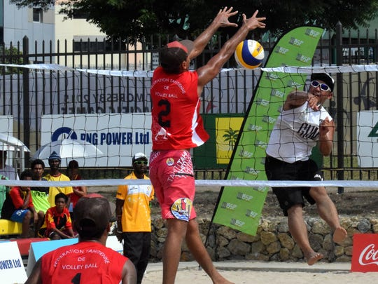 In this file photo, Guam men's national beach volleyballer Shintaro Okada breaks a spike through the net and the block during a match against Tahiti at the Sir John Guise beach courts at the Pacific Games in Port Moresby, Papua New Guinea.
