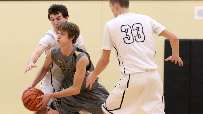Cascade's John Schirmer, center, looks for a pass while under pressure from Philomath's Brodie Marchant (33) and Jack Lehman during their game on Friday, Feb. 6 , 2015, in Philomath, Ore.
