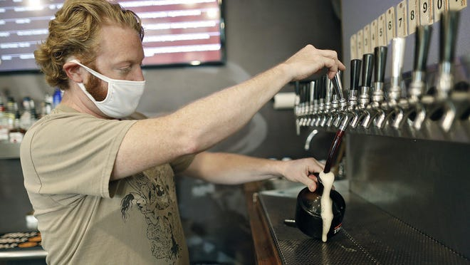 Justin Edwards pours a Southern Tier Pumking baby growler for takeout Wednesday at The Daily Growler on the Northwest Side. The Daily Growler used to offer beer delivery but has stopped because it was no longer financially viable.