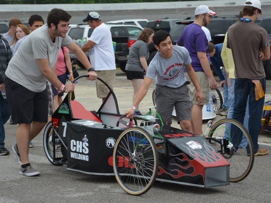 The Crestview High team members roll their car toward the starting line for the Emerald Coast Classic 120.