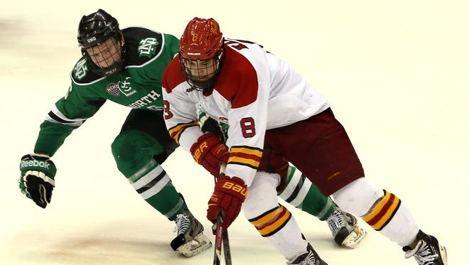 North Dakota's Paul LaDue (6) battles for the puck against Ferris State's Cory Kane (8).