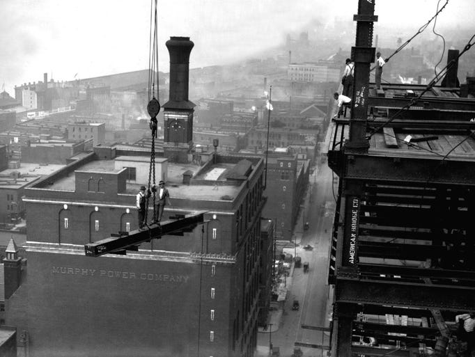 A worker rides a girder on the Ford Building, a 19-story