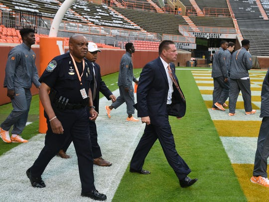 Sam Brown walks onto the field with Butch Jones before