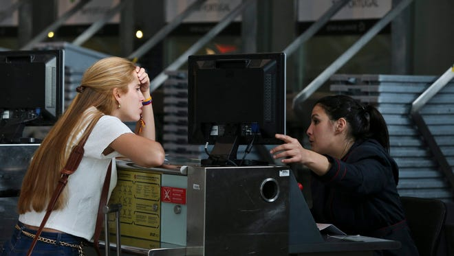 A passenger speaks with a clerk at the check-in counter for TAP Air Portugal at the Lisbon Airport on May 1, 2015, the first day of a 10-day pilot strike.