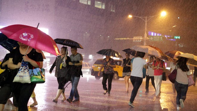 Pedestrians walk in a downpour brought by the outer rainbands of Typhoon Soudelor in Taipei, Taiwan, August 6, 2015.