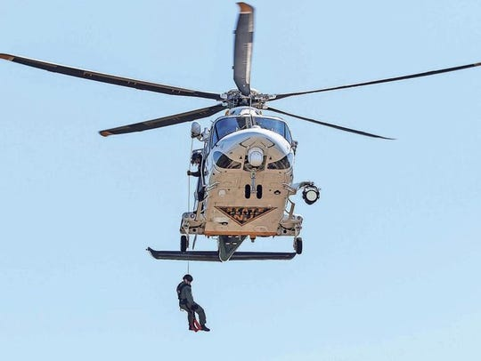 A NJ State Police Trooper lowers from a helicopter