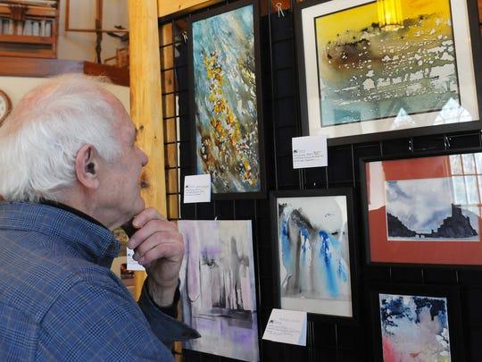 Gerhard Bernhard of Sister Bay views student art work at The Clearing Folk School's Winter Program exhibition.