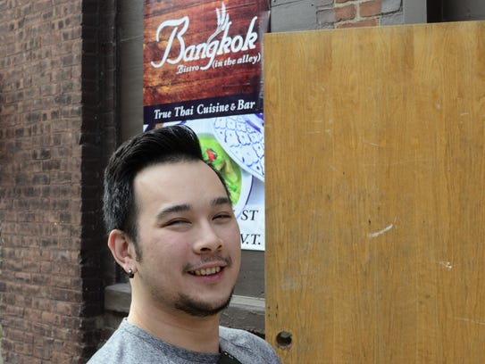 Bobby Chompupong stands by the entrance to his restaurant,