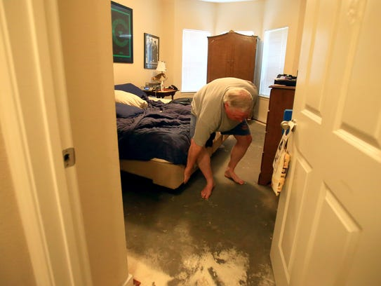 Danny Winston checks the bottom of his bed after water