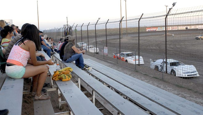 Spectators watch as modified race cars make their way around the track at Southern New Mexico Speedway in 2013. The owners of the speedway are proposing to build a new motorsports complex in Vado.