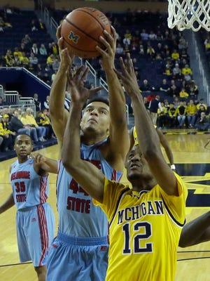 Michigan guard Muhammad-Ali Abdur-Rahkman, right, and Delaware State forward DeVaughn Mallory battle for a rebound Saturday, Dec. 12, 2015, in Ann Arbor.