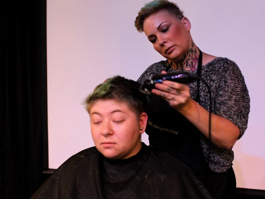 Eli Woolam gets a haircut from Alison Roberts from