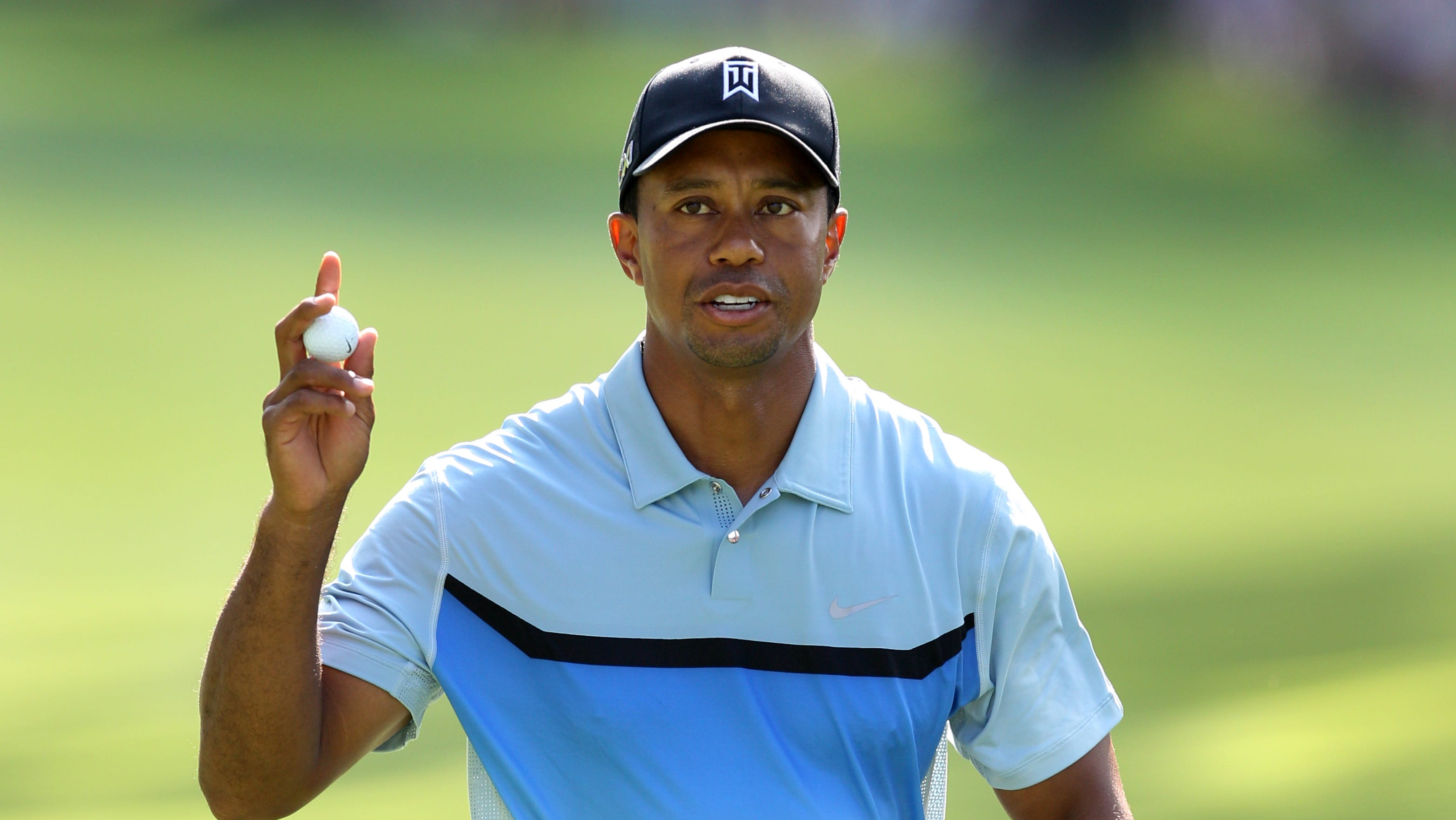 Tiger Woods waves after his birdie putt on 13.