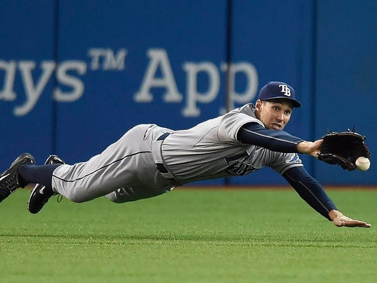 Tampa Bay Rays' Grady Sizemore just misses making a catch on a double by Toronto Blue Jays' Cliff Pennington during the second inning of a baseball game in Toronto on Friday, Sept. 25, 2015. (Frank Gunn/The Canadian Press via AP)