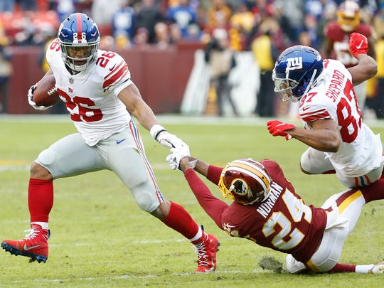 Dec 9, 2018; Landover, MD, USA; New York Giants running back Saquon Barkley (26) carries the ball past Washington Redskins cornerback Josh Norman (24) in the second quarter at FedEx Field. The Giants won 40-16. Mandatory Credit: Geoff Burke-USA TODAY Sports