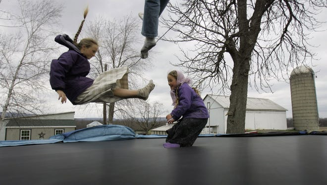 Children jump on a trampoline.