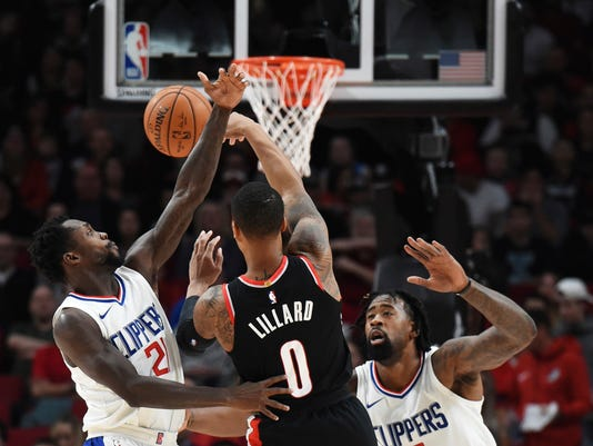 Portland Trail Blazers guard Damian Lillard (0) passes the ball over Los Angeles Clippers guard Patrick Beverley during the first quarter of an NBA basketball game in Portland, Ore., Thursday, Oct. 26, 2017. (AP Photo/Steve Dykes)