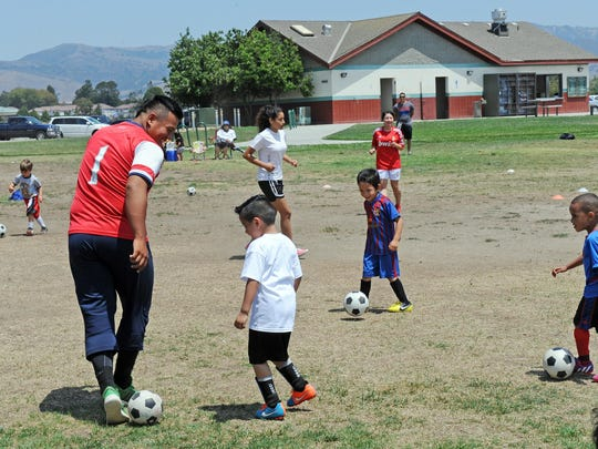 The youngest participants in the city of Salinas/Hartnell College summer soccer camp try to tag their coaches with the ball.