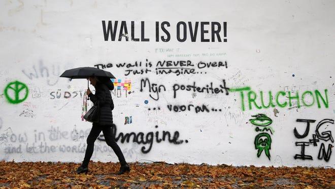 "A woman walks past Prague's ""John Lennon Wall"" that was recently painted white in Prague, Czech Republic on  Nov. 18."