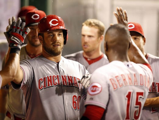 Cincinnati Reds relief pitcher J.J. Hoover (60) receives a high-five in the dugout after scoring a run against the Pittsburgh Pirates during the ninth inning at PNC Park.