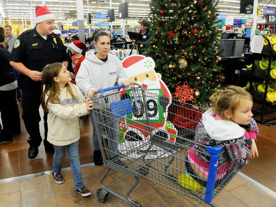 MIKE LAWRENCE / THE GLEANER   (L-R) Henderson Police Chief Chip Stauffer, Abbi Embry, 8 years-old, Megan Embry and Shauna Embry, 5 years-old, head out into the Henderson Wal-Mart Tuesday evening for the annual Fraternal Order of Police Cops & Kids Christmas shopping, December 15, 2015.