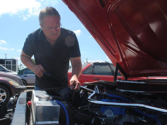 Dave Marsland inspects his 1966 Ford Mustang at a tow