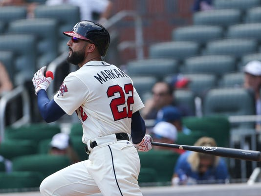 Atlanta Braves right fielder Nick Markakis (22) follows through on a two-run double int he second inning of a baseball game against the Cincinnati Reds, Sunday, Aug. 20, 2017, in Atlanta. (AP Photo/John Bazemore)