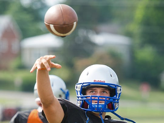 Robert E. Lee High School quarterback Stephen Baker passes the football during their practice on Monday, Aug. 18, 2014.