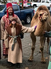 Cast members from Christ Lutheran Church's annual living nativity event walk with a camel named Sadie during this year's Milford Christmas parade.