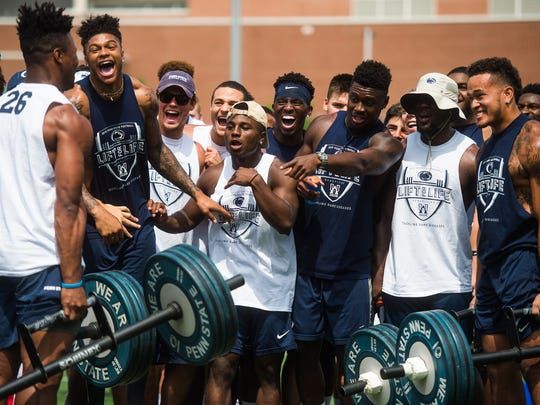 Teammates react as Saquon Barkley, left, and Koa Farmer, right compete in the farmers carry competition Saturday July 16, 2016 during the 14th annual Lift for Life at Penn State University.