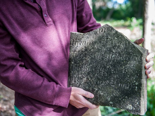 Darrin Silvester, 44, of Canton holds one of the oldest grave markings from the cemetery. Sylvester has spent the last 11 years working with students to restore the once overgrown cemetery.