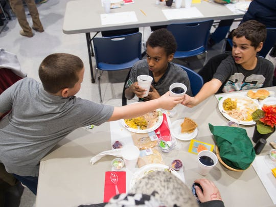 Tyson Cleary, a volunteer, hands juice to Makye Bonitto and David Thomas on Thanksgiving, Nov. 24, 2016 at the Salvation Army in Chambersburg, Pa.