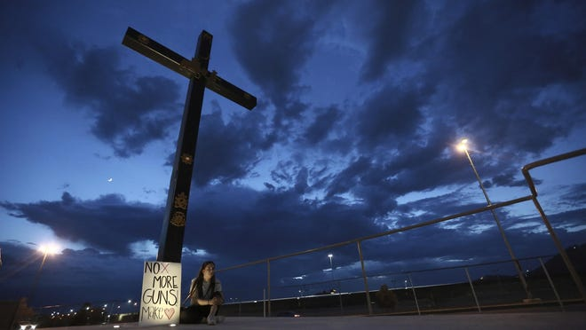 A woman sits next to a sign with a message that reads: ¨No More Guns! Make Love¨, in Juarez, Mexico, Saturday, Aug. 3, 2019, where people are gathering for a vigil for the 3 Mexican nationals who were killed in an El Paso shopping-complex shooting. Twenty people were killed and more than two dozen injured in a shooting Saturday in a busy shopping area in the Texas border town of El Paso, the state's governor said. (AP Photo/Christian Chavez)