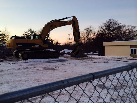 A crane rests at 308 Grand Ave. on Jan. 22, 2015. Next to it sits a building that used to house 5 Loaves & 2 Fish Christian Bookstore which will be demolished for a Kwik Trip gas station and convenience store to occupy both sites.